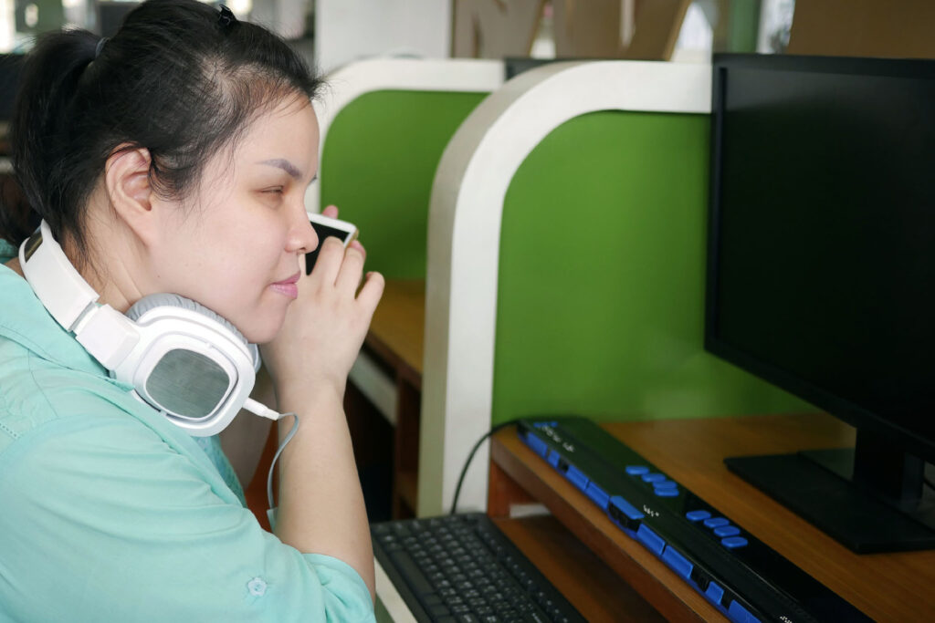assistive technology blind woman with headphone using computer with refreshable braille display
